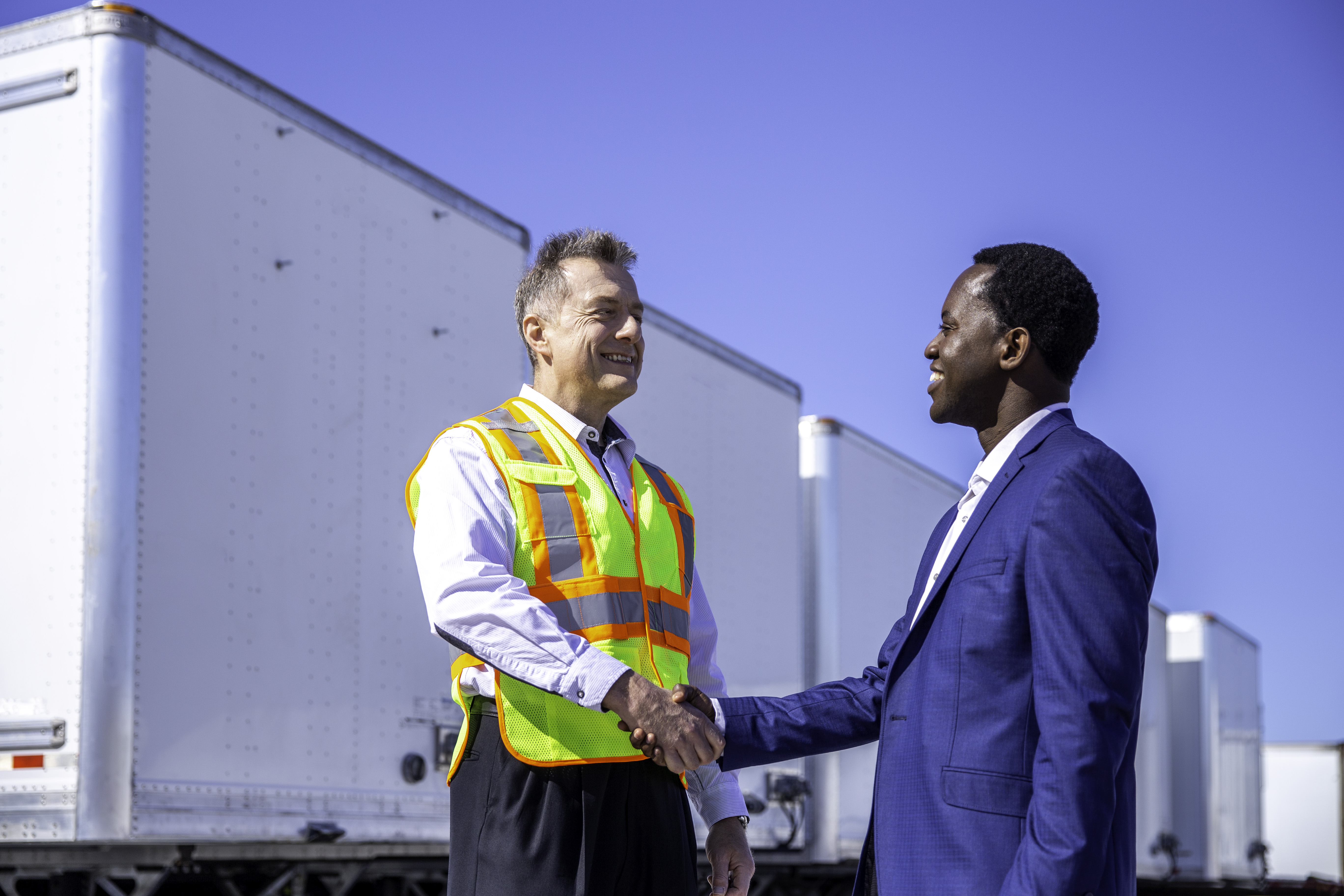 Two men shaking hands besides trailers