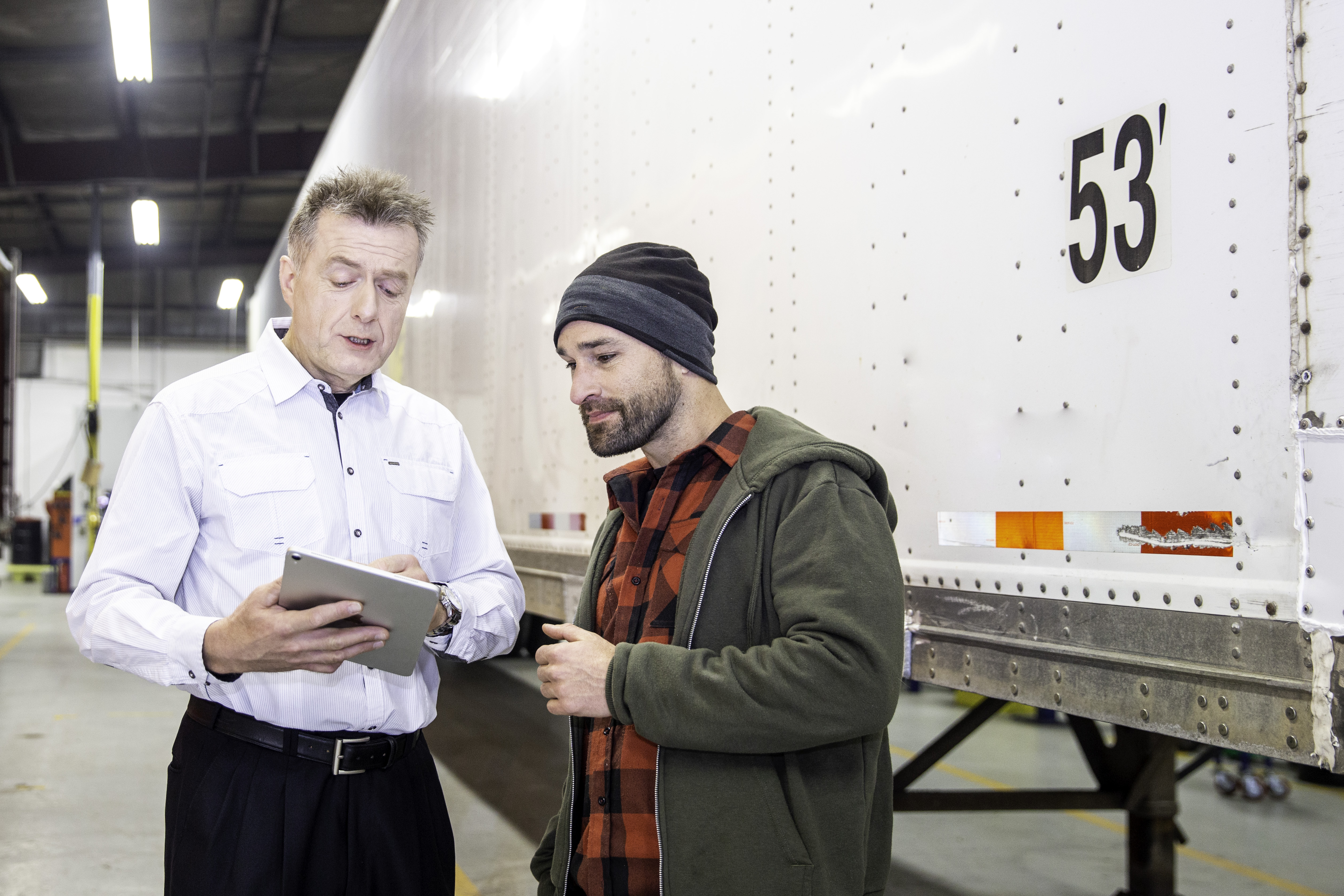 Man teaching other man with Ipad